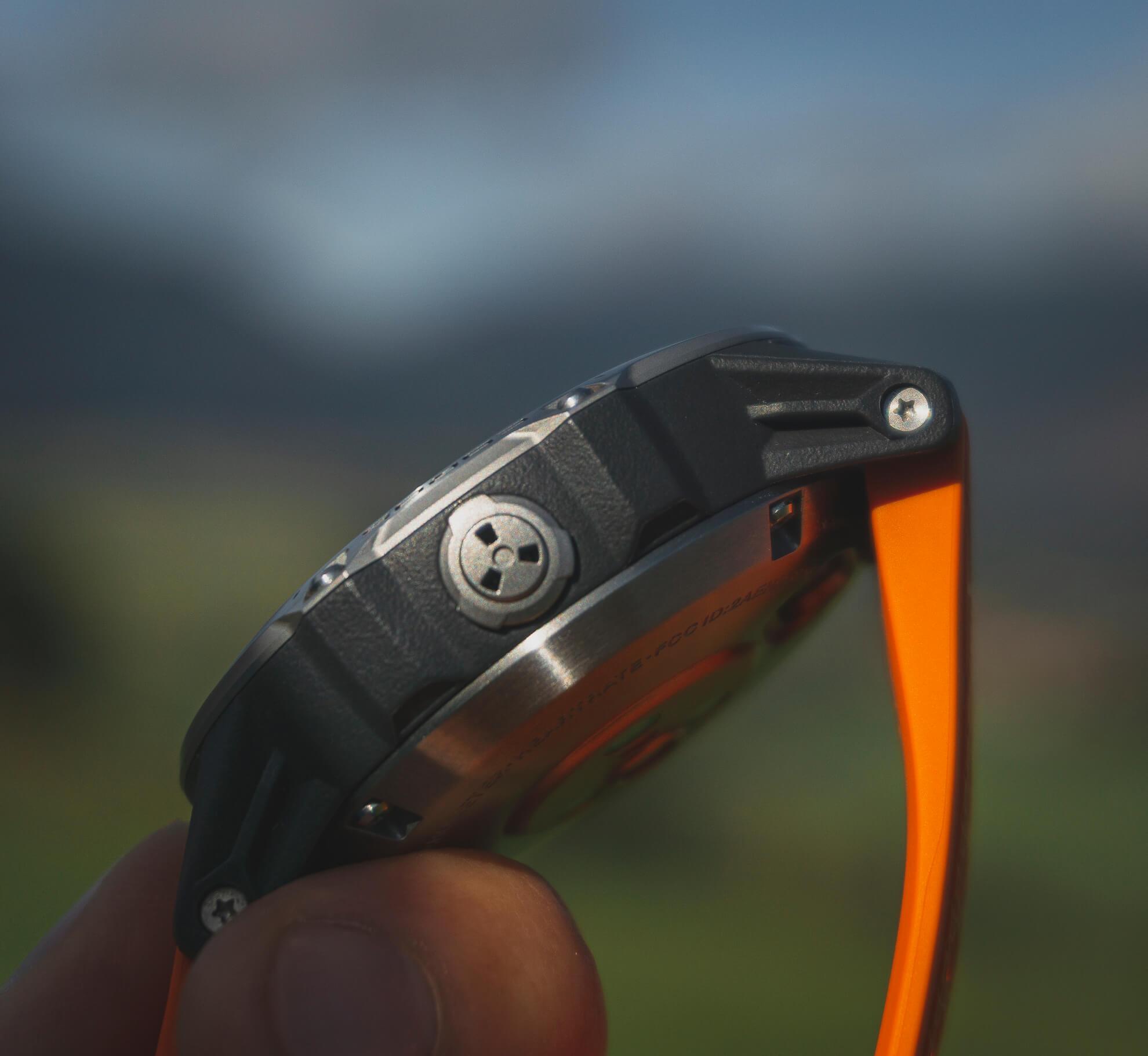 Detail kovového otvoru na boku tela hodiniek, pod ktorým sa skrýva senzor merania barometrického tlaku.